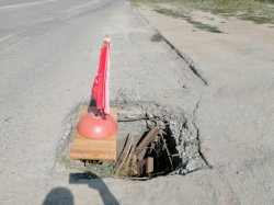 Провал на дороге заделали красным победным флажком